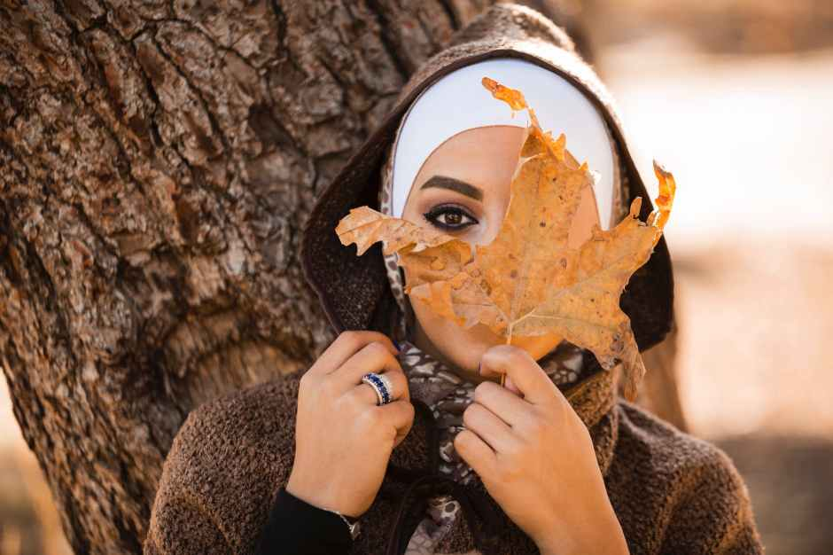 woman leaning on brown tree holding brown leaf covering her face