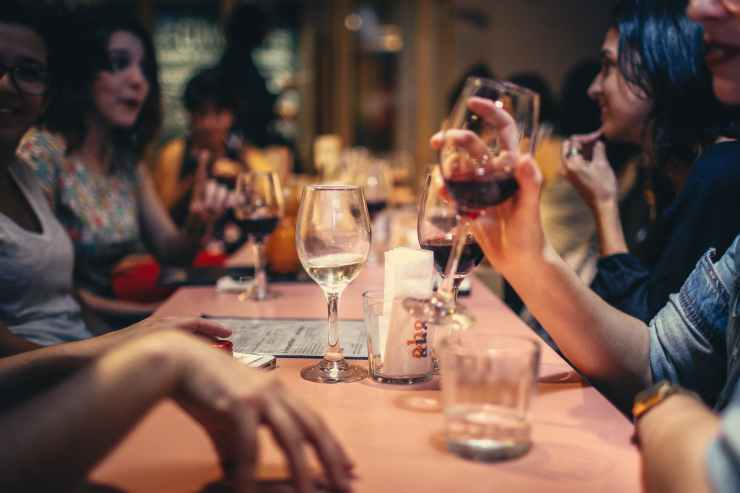 people drinking liquor and talking on dining table close up photo